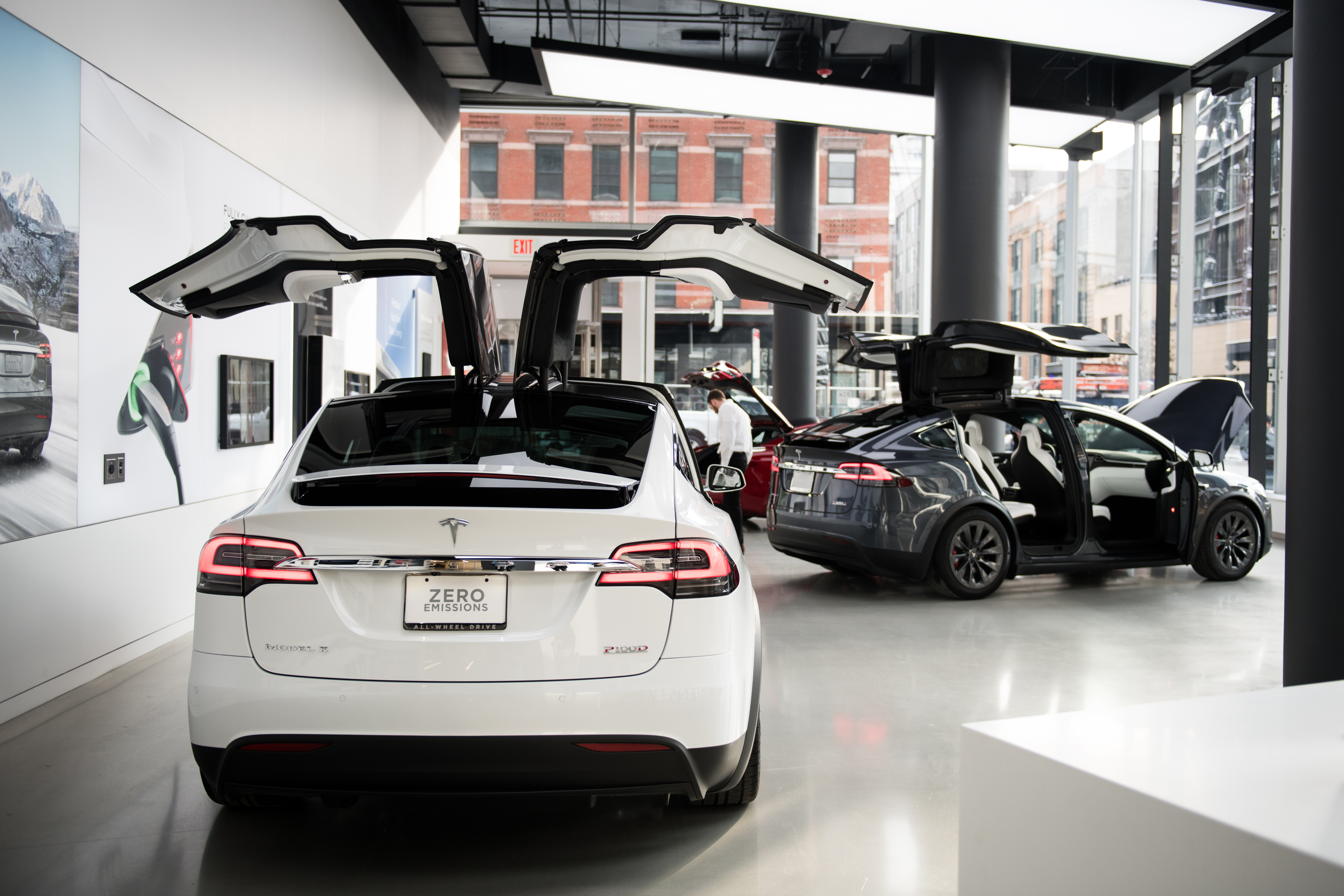 A Tesla Inc. Model X P100D sports utility vehicle (SUV), left, sits on display at the company's new showroom in New York, U.S., on Thursday, Dec. 14, 2017. The Meatpacking District location, which opens to the public at 11 a.m. Friday, lets customers for the first time explore energy offerings, configure cars and place orders all under one roof. Photographer: Mark Kauzlarich/Bloomberg via Getty Images